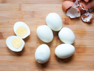 Peeled eggs on a wooden board with one egg cut in half