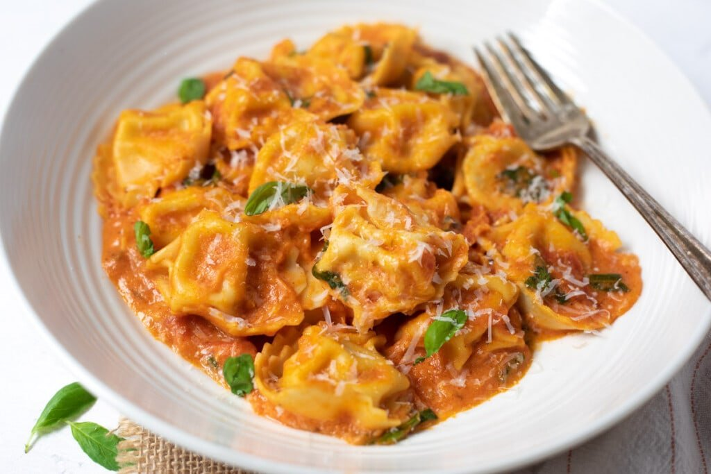 Cheesy Tomato Tortellini served in a bowl topped with basil and parmesan