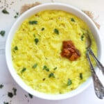 plain khichdi made with moong dal and rice served in a bowl topped with ghee, cilantro and pickle