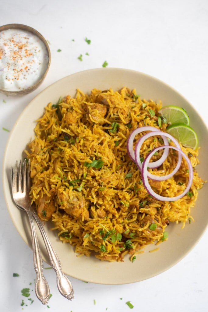 Chicken Biryani served in a plate garnished with onions, lime along with a side of raita