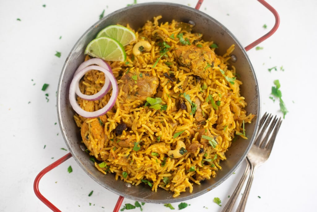 Chicken Biryani served in a platter garnished with onions and limes