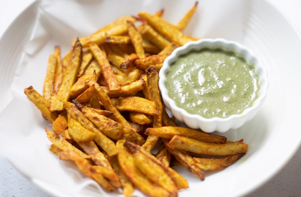 Taro Fries in a bowl with a green dip / chutney