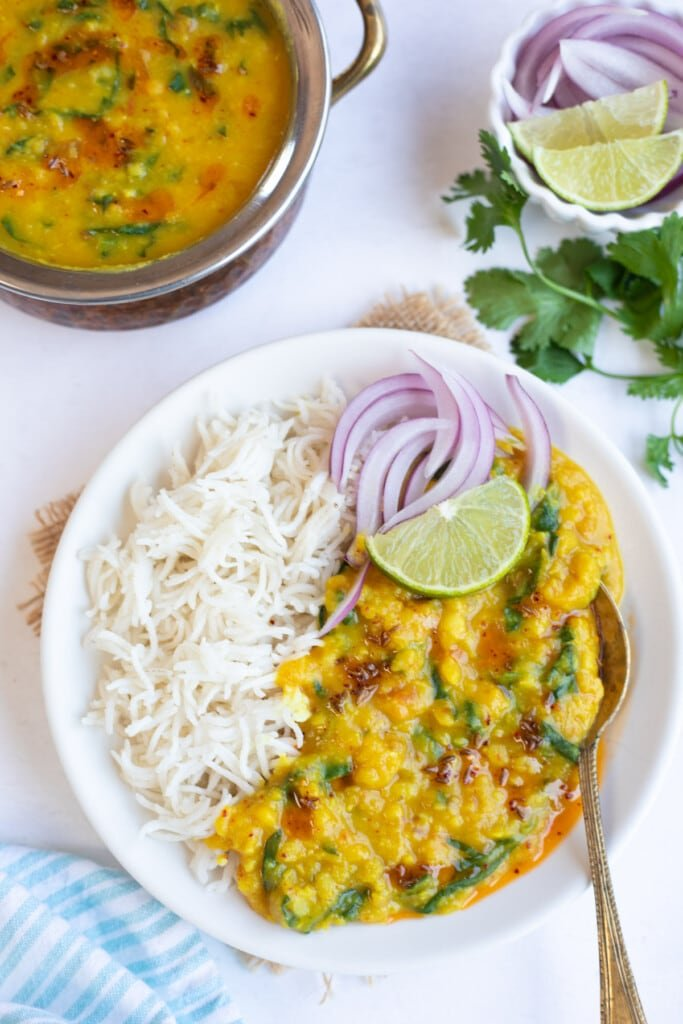 Spinach dal served with rice garnished with onions and lime