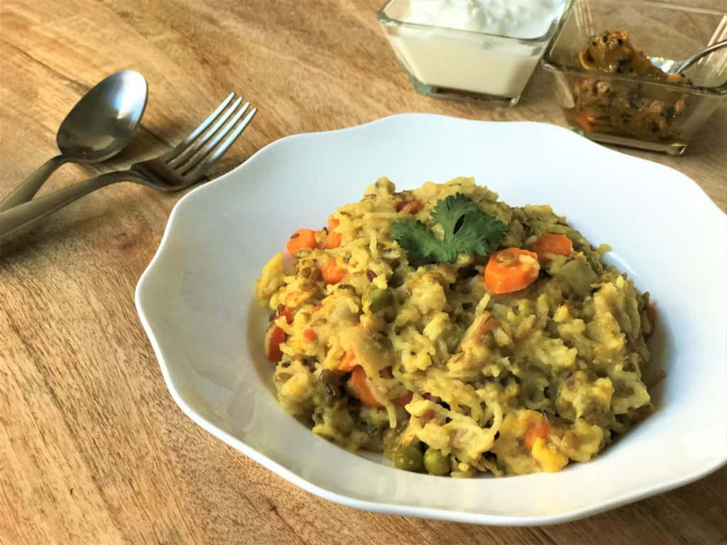 Masala Khichdi made in the Instant Pot in a bowl along with yogurt and pickle.
