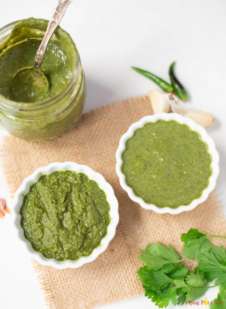 Green cilantro mint chutney in two bowls and a glass jar.