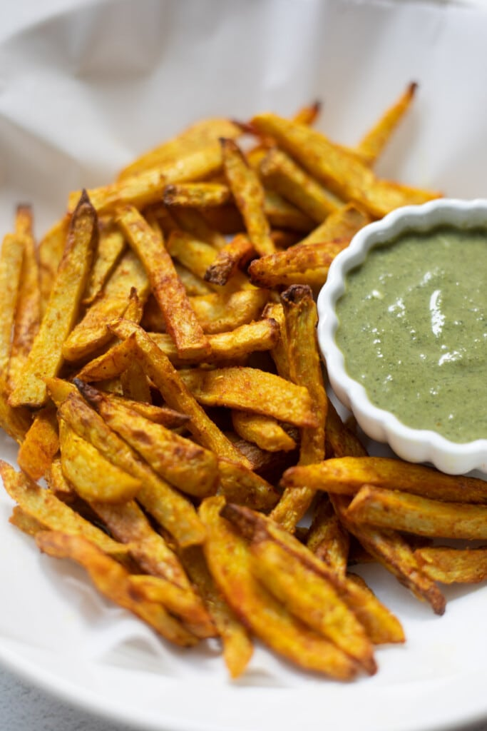 Taro fries in a white bowl with a creamy dip