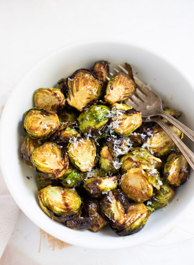 Roasted Air Fryer Brussels sprouts in a white bowl topped with parmesan