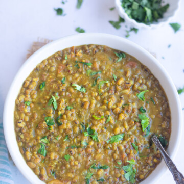 Green Moong Dal curry in a bowl garnished with cilantro