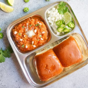Pav Bhaji served in a plate with onions and lime on the side