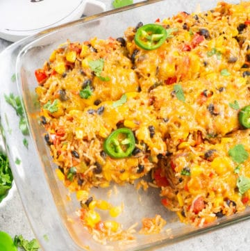 Healthy Vegetarian Mexican Rice & Bean Casserole is easy to make and filled with cheesy goodness, along with brown rice and lots of veggies. This is an easy gluten free & vegetarian casserole for a weeknight dinner or your next party!