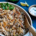 Instant Pot Lentils and Rice (Mujadara) in a serving bowl with yogurt and lemon on the side.