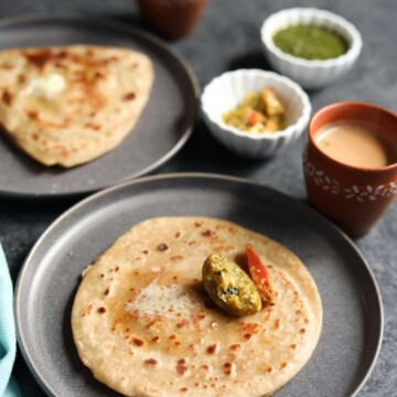 Paratha, pan fried indian flatbread along with pickle and chai