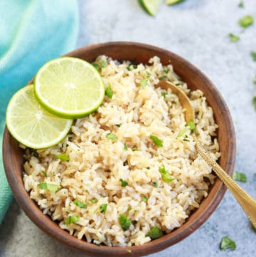 Instant Pot Cilantro Lime Brown Rice served in a brown bowl with lime slices and a spoon