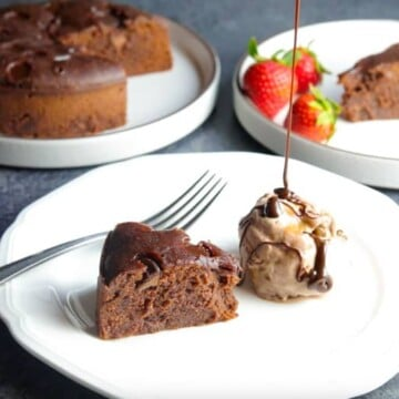 A piece of Instant Pot Brownie in a plate with ice-cream and chocolate sauce dripping, and the whole brownie cake in the back.