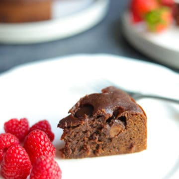 A piece of Instant Pot Brownie in a plate with raspberries, and the whole brownie cake in the back.