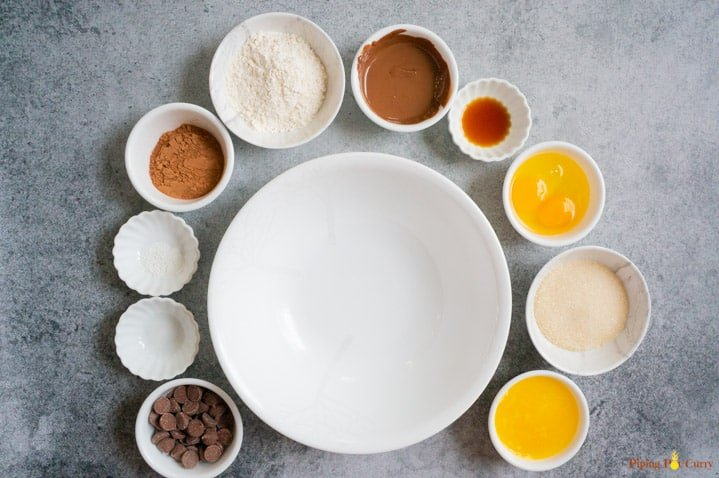 Ingredients to make instant pot brownie in small bowls around a large white bowl