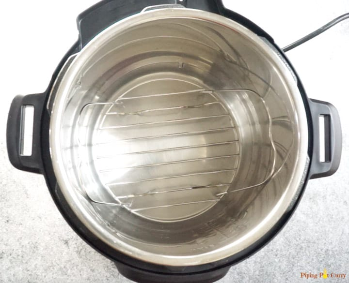 Instant pot filled with water and a trivet ready to make brownies in the instant pot