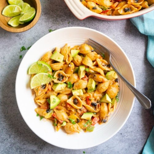 Shell Pasta topped with avocado and lime in a white bowl