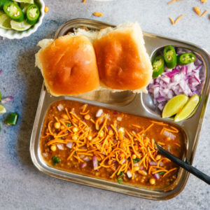 Curry topped with crunchy farsan served with dinner rolls (pav) and onions/lime on the side