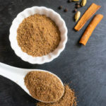Chai Masala Spice Mix in a white bowl and spoon along with some whole spices
