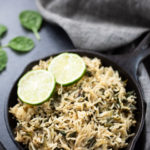 Spinach Rice in a cast-iron pan topped with lemon slices