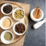Whole spices in small white bowls