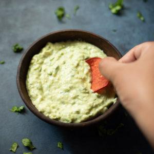 Dipping a chip in a creamy avocado sauce
