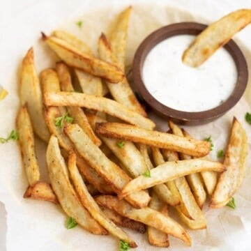 French Fries with a fry dipped in a yogurt dipping sauce