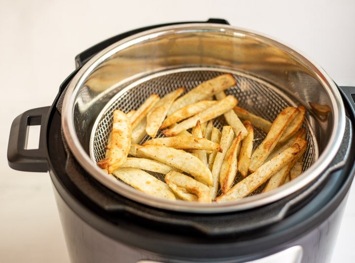 Crispy French Fries in a mesh basket in an electric pressure cooker