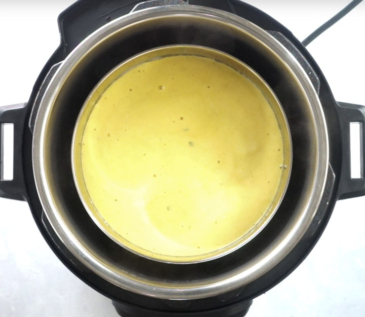 Yellow batter in a steel container ready to be steamed
