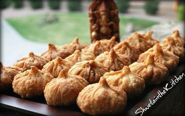 Fried Modak or dumplings in front of Lord Ganesha idol