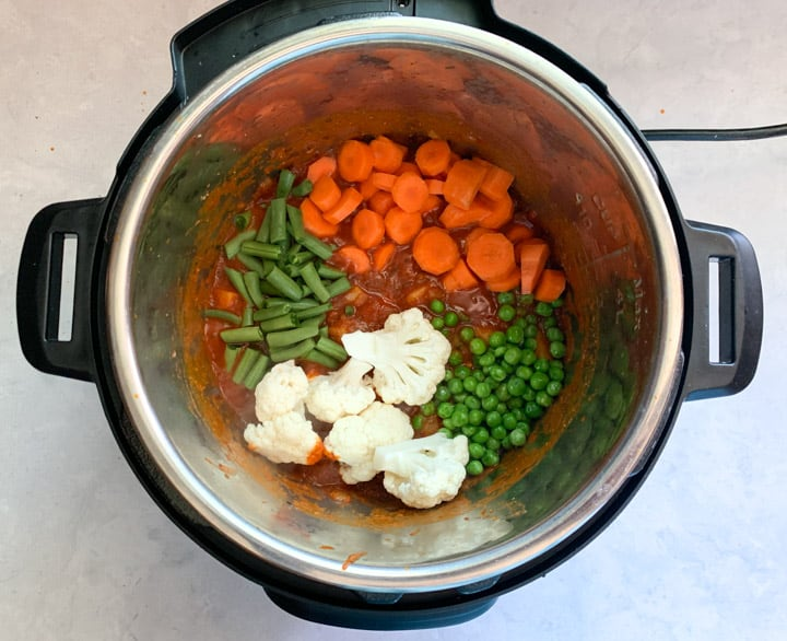 Variety of veggies added to a curry base in instant pot