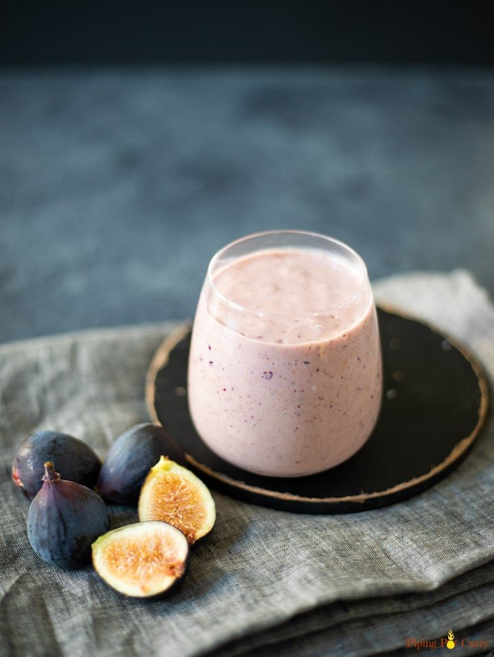 Fig smoothie in a glass with figs lying around