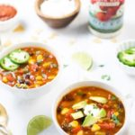 Two bowls of taco soup along with toppings spread out