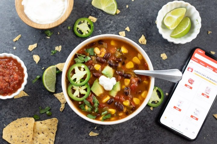 A bowl of taco soup with lots of toppings on the side