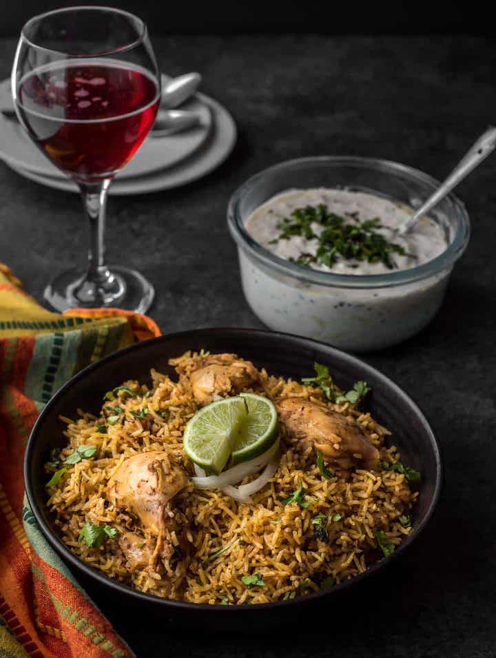 Chicken Biryani in a bowl with raita and wine