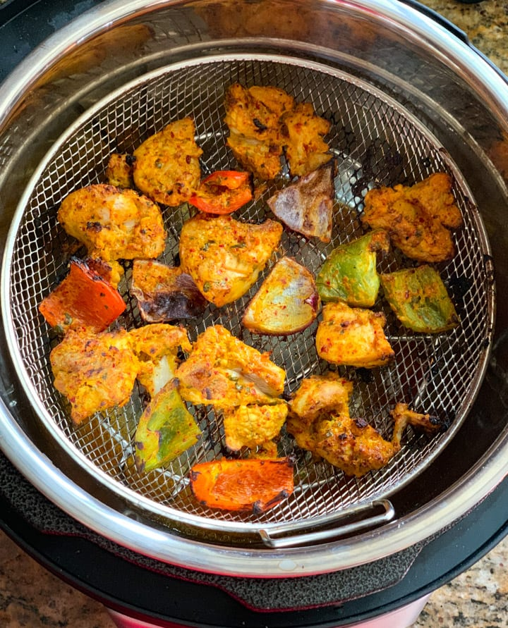 Cooked chicken tikka bites in a air fryer attachment for pressure cooker
