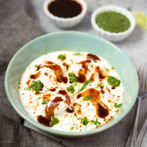 Dahi vada chaat with chutneys in small white bowls