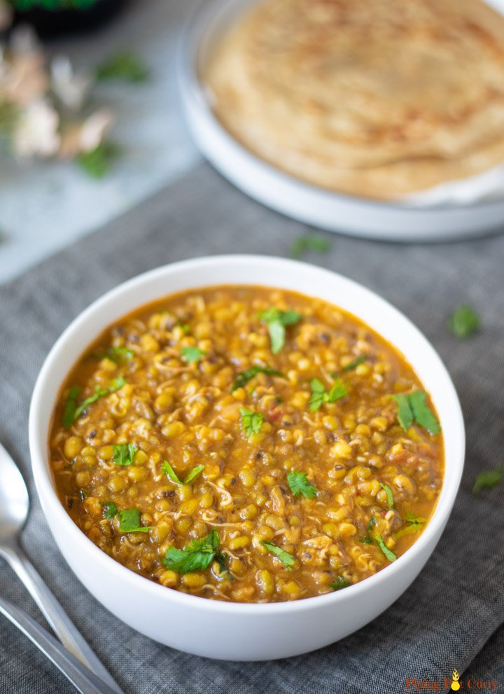 Moong Sprouts Curry in a white bowl with parathas in a plate