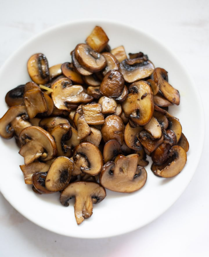 Sautéed browned cremini mushrooms on a white plate
