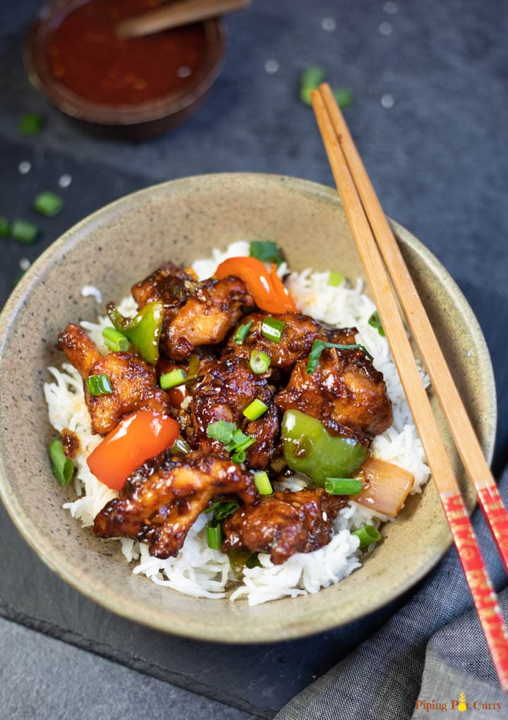 Chilli Chicken over white rice in a bowl, with spicy chili sauce in a small bowl
