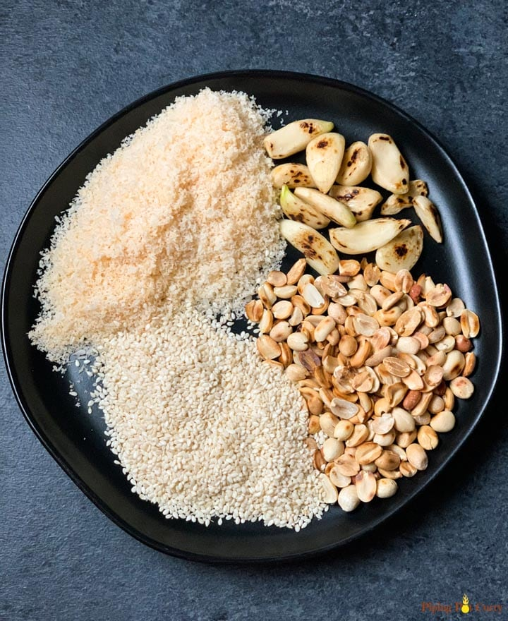 Ingredients such as roasted garlic, peanuts, sesame and coconut powder in a black plate