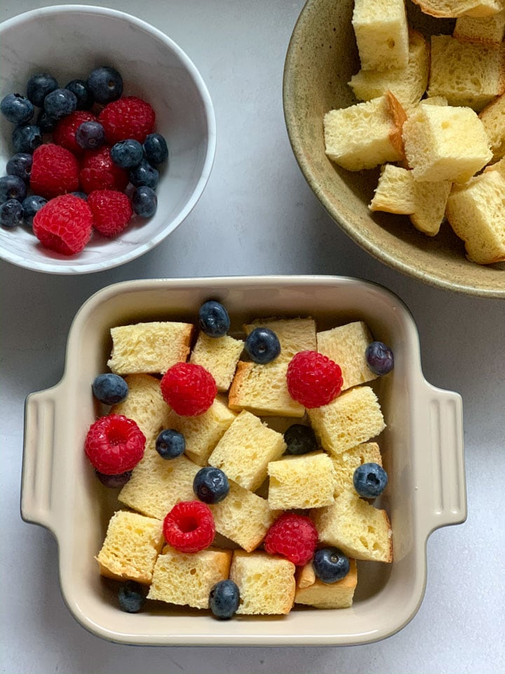 Brioche pieces and berries in a baking pan