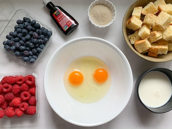 ingredients such as eggs, berries, brioche and sugar to make pudding