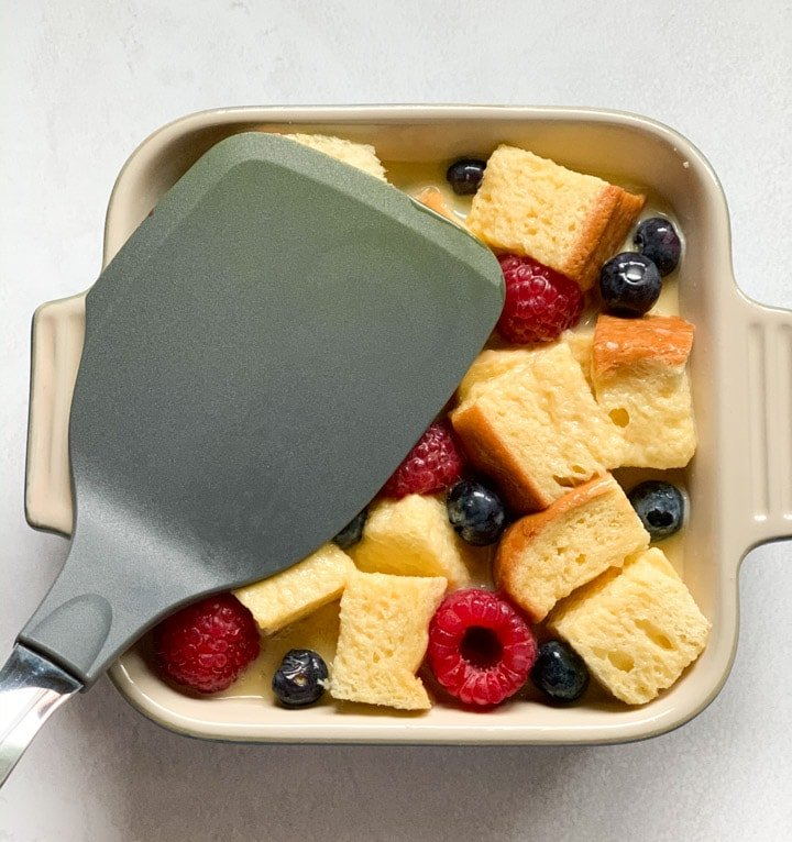 Pressing brioche and berries in a baking pan with a spatula so that they soak the custard