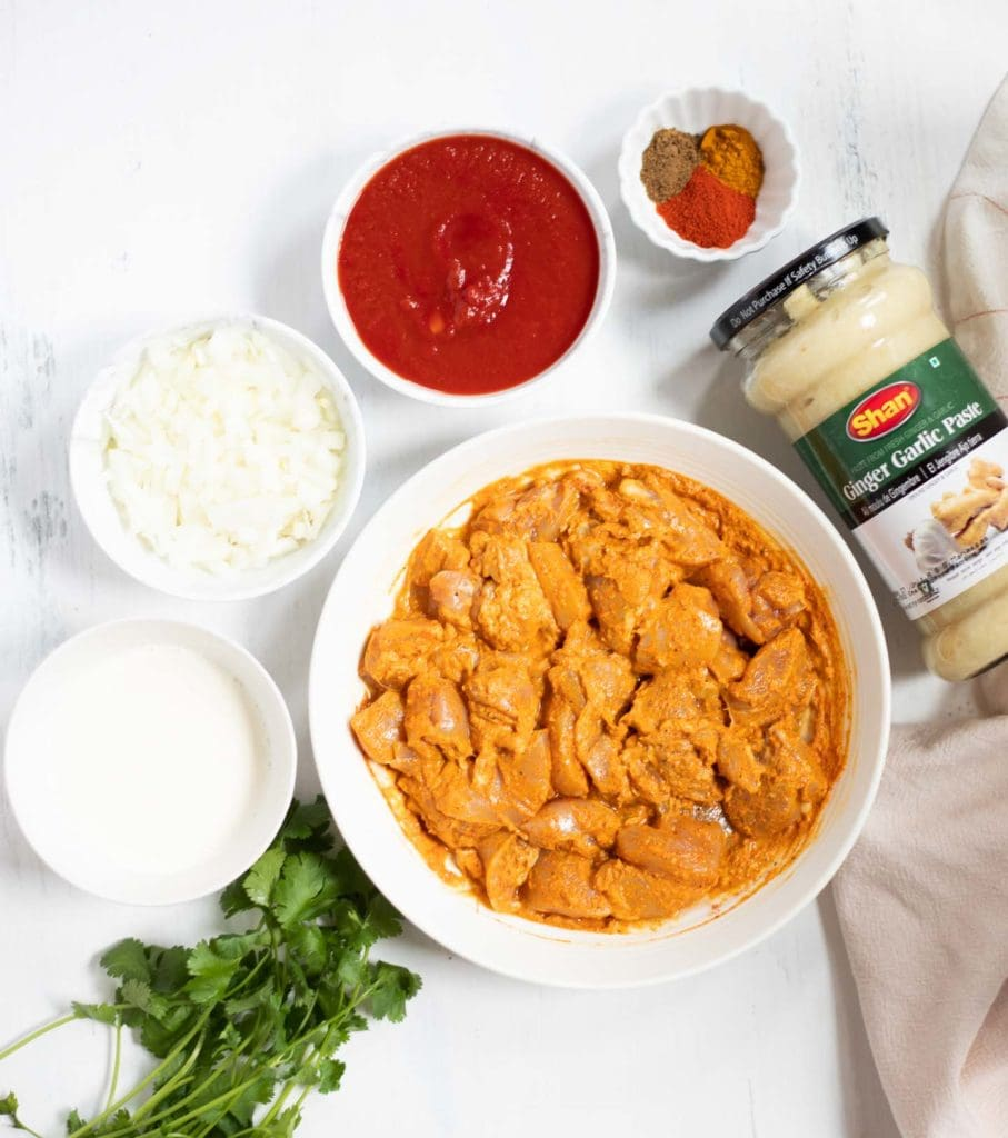 Ingredients such as marinated chicken, onions, tomato, ginger garlic, cilantro and spices