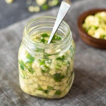 Adrak ka achar. Ginger green chili pickle in a glass bottle