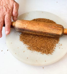Some ground cumin on a marble with a rolling pin