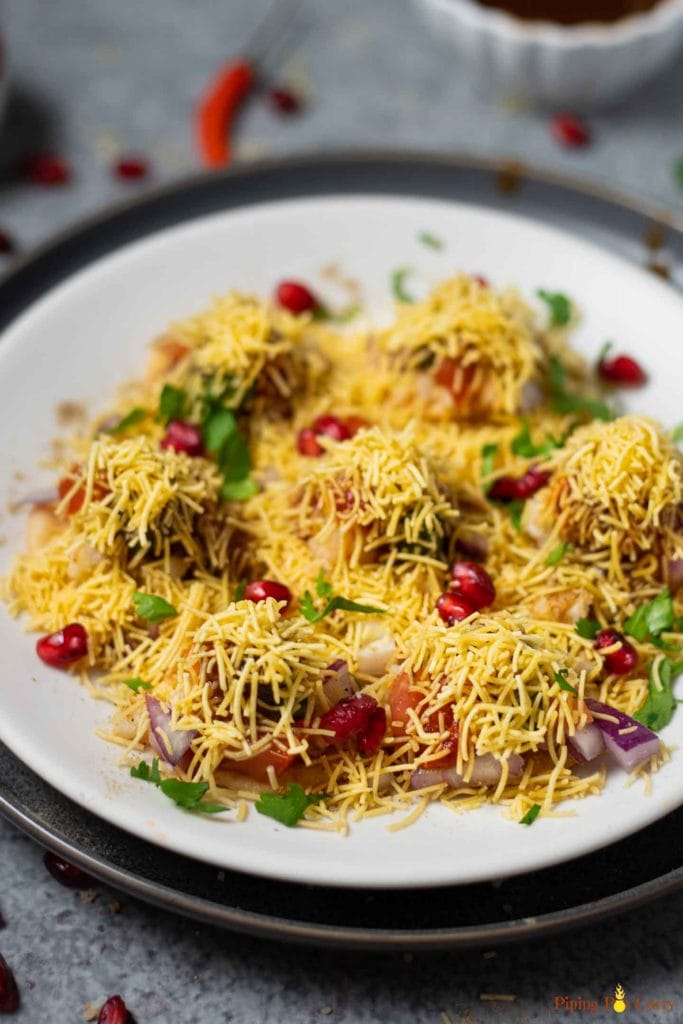 Sev puri garnished with cilantro and pomegranate seeds on a white plate