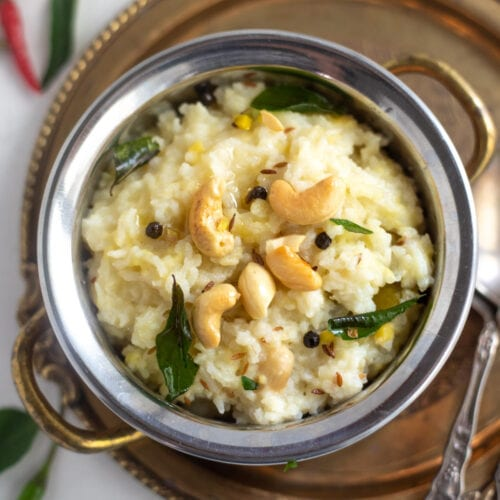Ven Pongal in a bowl garnished with cashews and curry leaves